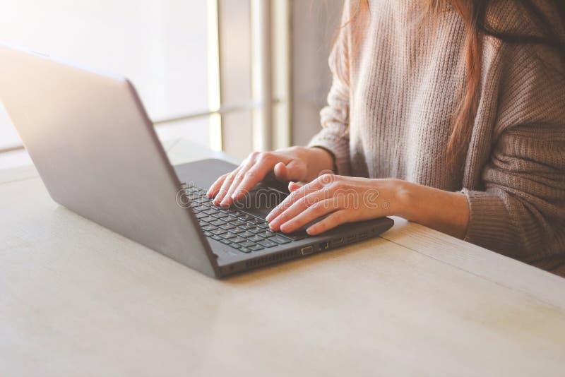 在家工作的妇女或在键盘膝上型计算机的办公室手 免版税库存照片