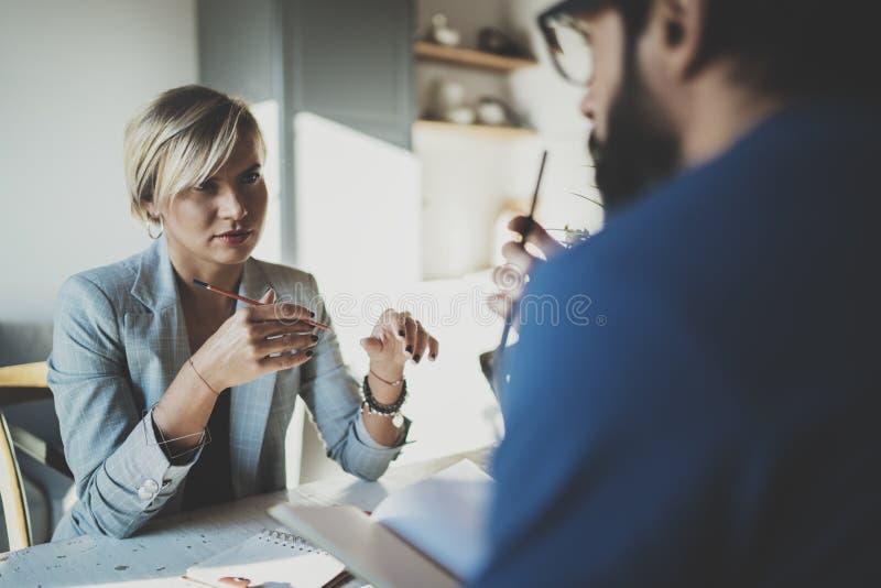 在家工作过程的工友 工作与有胡子的同事人一起的年轻白肤金发的妇女在现代家庭办公室 免版税库存图片