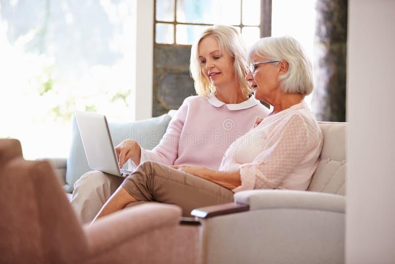 在家帮助有计算机的成人女儿资深母亲 免版税库存照片