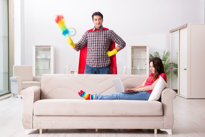 在家帮助他的妻子的超级英雄丈夫 库存照片