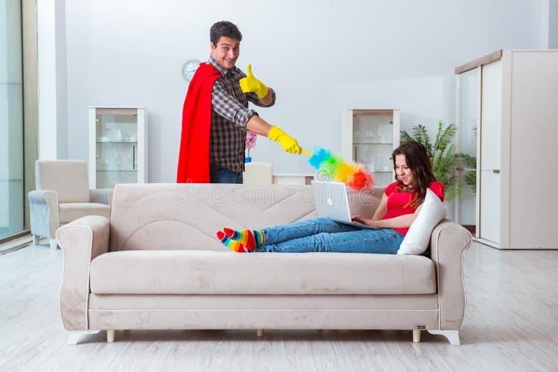 在家帮助他的妻子的超级英雄丈夫 免版税图库摄影