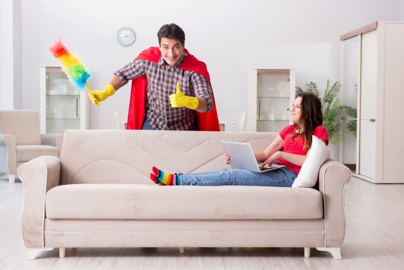 在家帮助他的妻子的超级英雄丈夫 免版税库存照片