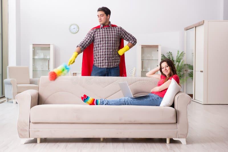 在家帮助他的妻子的超级英雄丈夫 库存图片