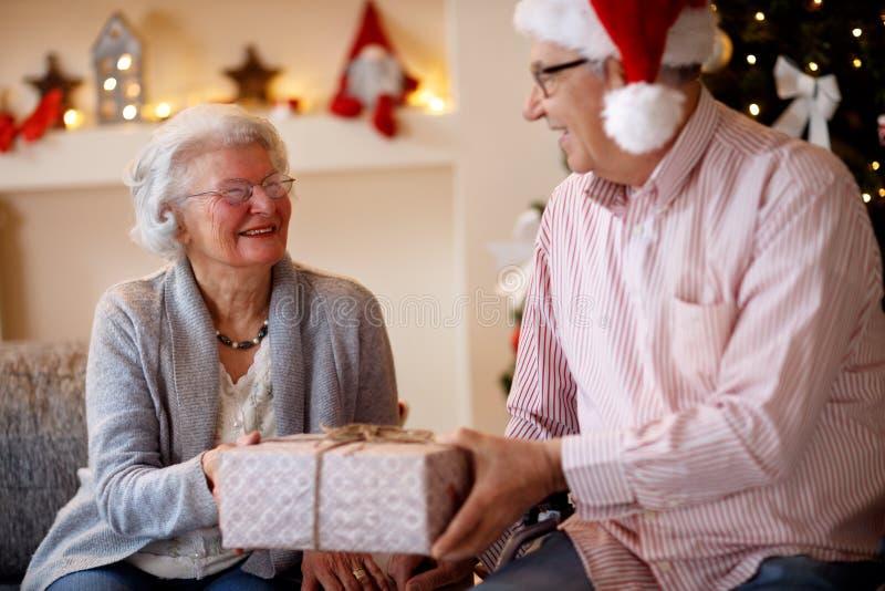 在家庆祝圣诞节与pres的美好的年长夫妇 免版税库存照片