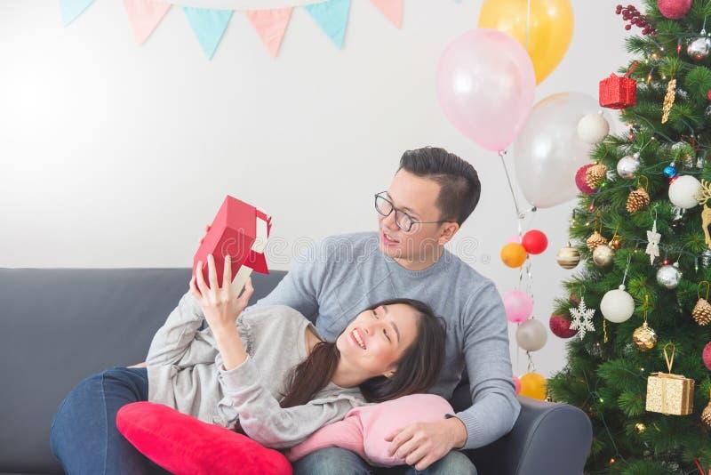 在家庆祝圣诞节的年轻夫妇 给他的女朋友礼物盒的帅哥 图库摄影