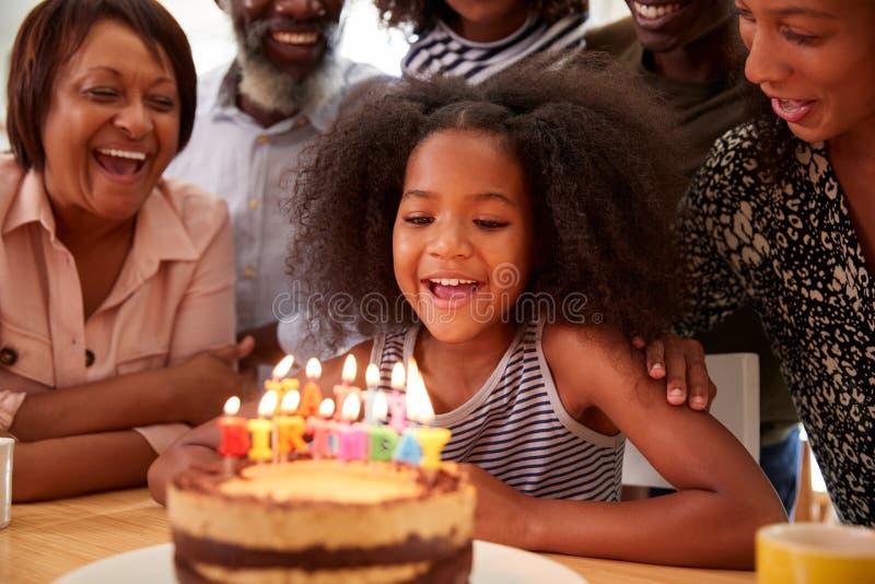 在家庆祝孙女生日与蛋糕和蜡烛的多代的家庭 图库摄影