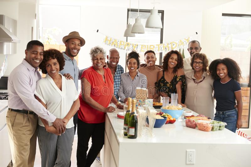在家庆祝的中间年迈的非裔美国人的人打开的香槟与他的三一代家庭 免版税图库摄影