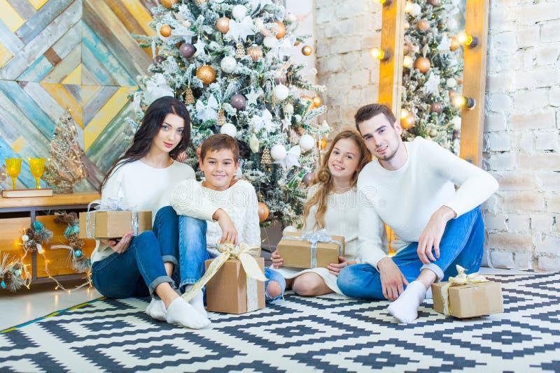 在家庆祝的家庭 父亲、母亲和孩子圣诞树的背景的与礼物坐 免版税图库摄影
