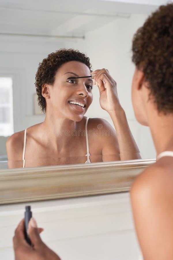 在家应用在镜子的妇女染睫毛油 库存照片