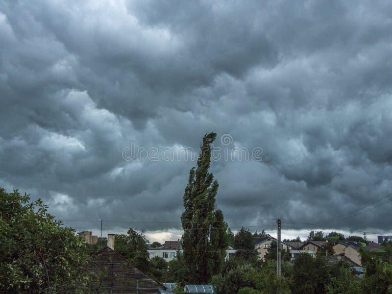 在家庭下的深蓝风雨如磐的天空 背景 免版税库存照片