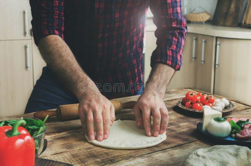 在家庭厨房里供以人员面团为烹调自创薄饼做准备 免版税库存照片