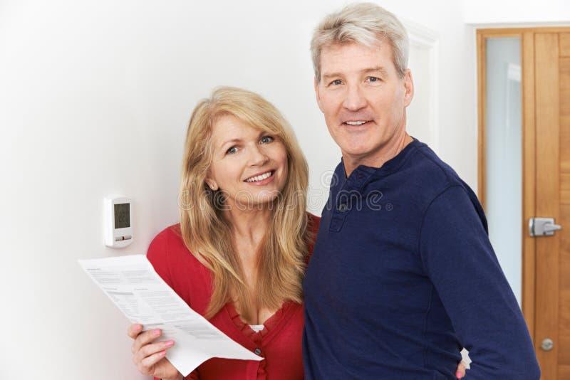 在家庭取暖票据的成熟夫妇挽救金钱 免版税库存图片