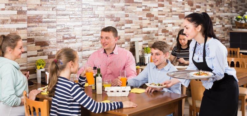 在家庭咖啡馆的快乐的深色的女服务员服务家庭 库存照片