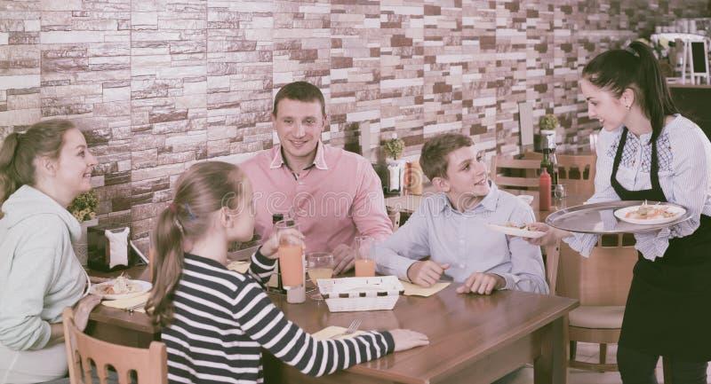 在家庭咖啡馆的愉快的深色的女服务员服务家庭 库存照片