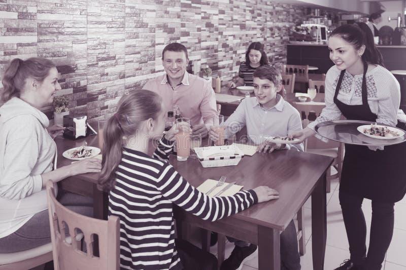 在家庭咖啡馆的年轻深色的女服务员服务家庭 免版税库存照片
