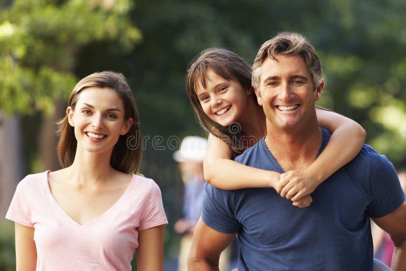 给在家庭步行的爸爸女儿肩扛通过夏天公园 免版税库存照片