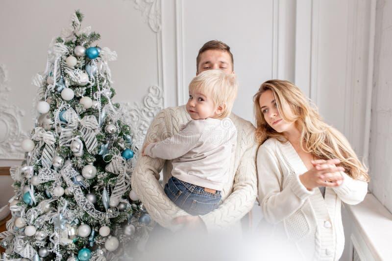 在家庭的父亲、怀孕的母亲和他们的小儿子的愉快的家庭画象 新年好 圣诞节装饰了结构树 免版税库存图片
