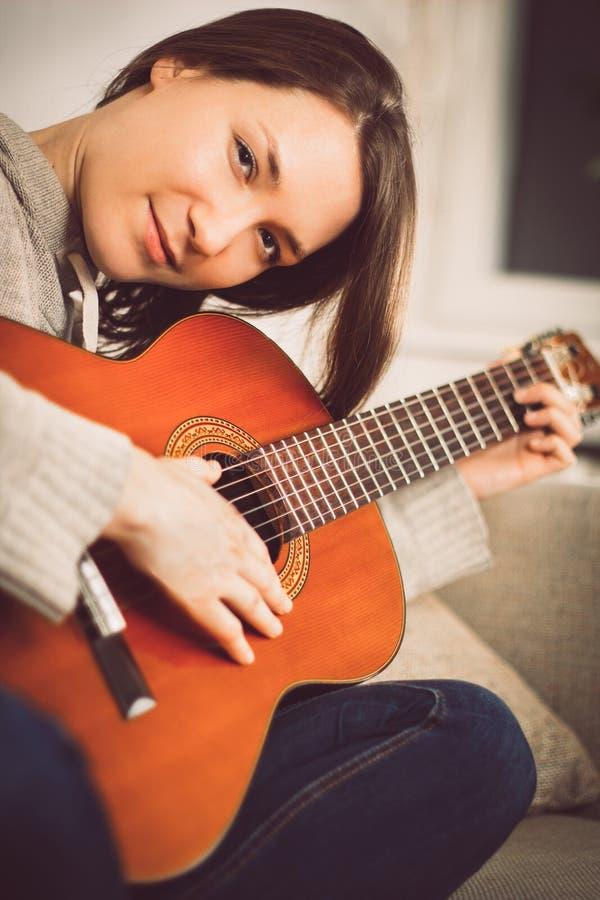 在家弹吉他的少妇 有乐器画象的轻松的愉快的少妇 免版税库存照片