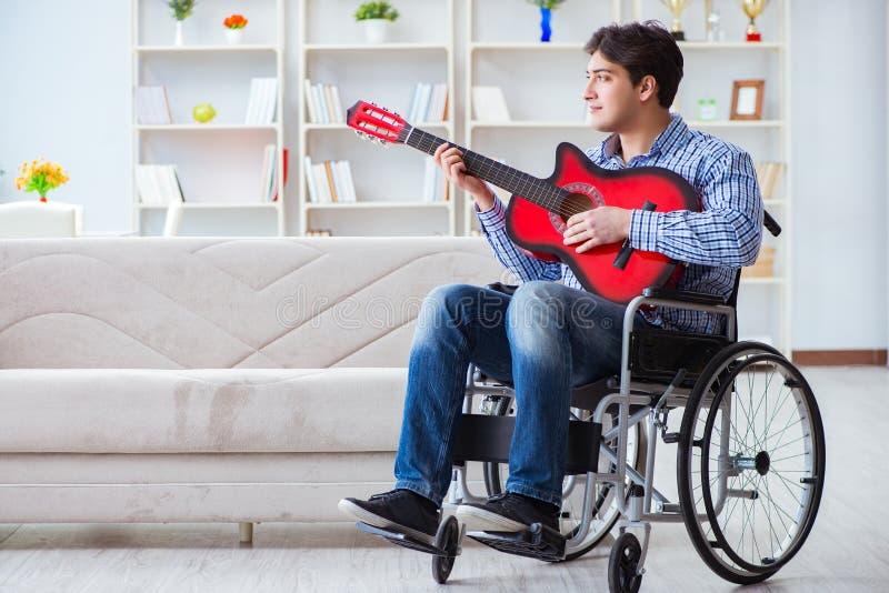 在家弹吉他的残疾人 免版税库存照片