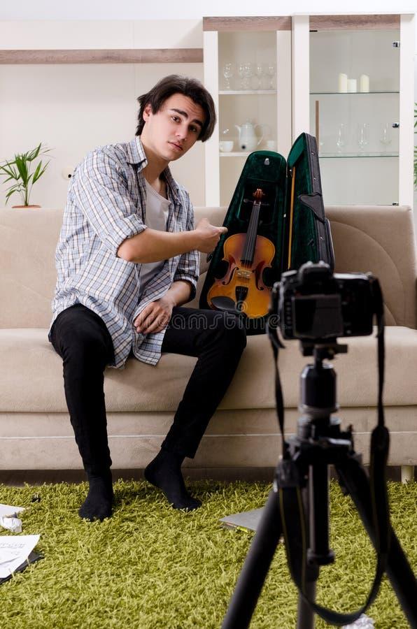 在家弹小提琴的年轻男性博客作者 库存图片