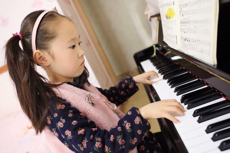 在家弹钢琴的小女孩 免版税库存照片