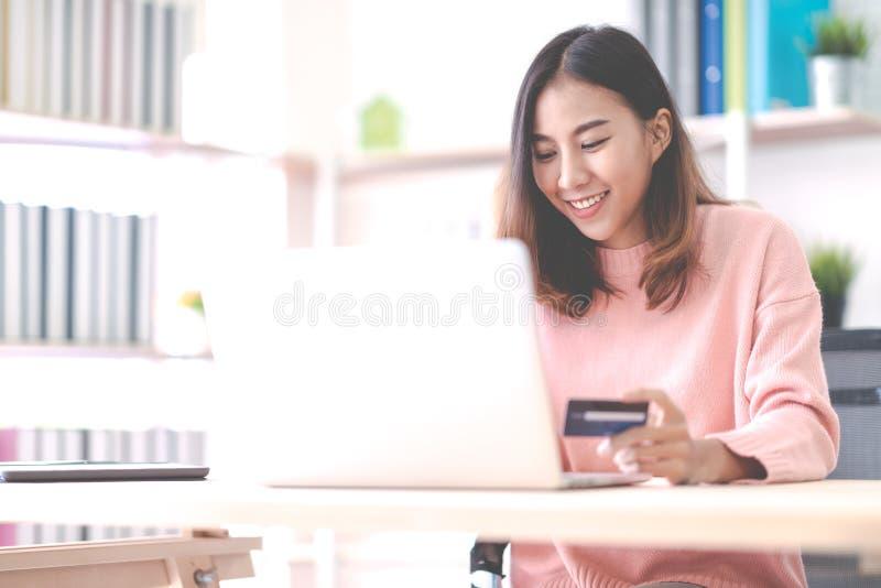 在家微笑和坐办公室的年轻愉快的可爱的亚裔女生、企业主、企业家或者自由职业者后边 图库摄影