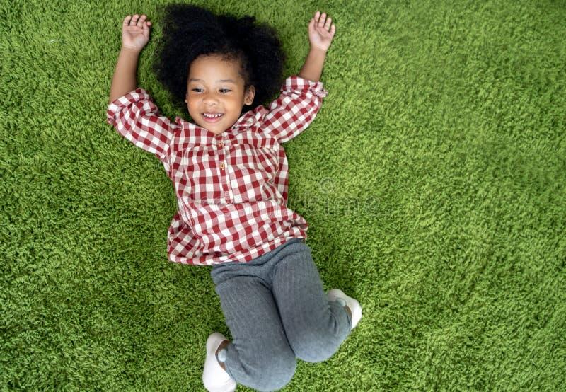 在家微笑和放置在绿色地毯地板上的愉快的儿童孩子在客厅 免版税图库摄影