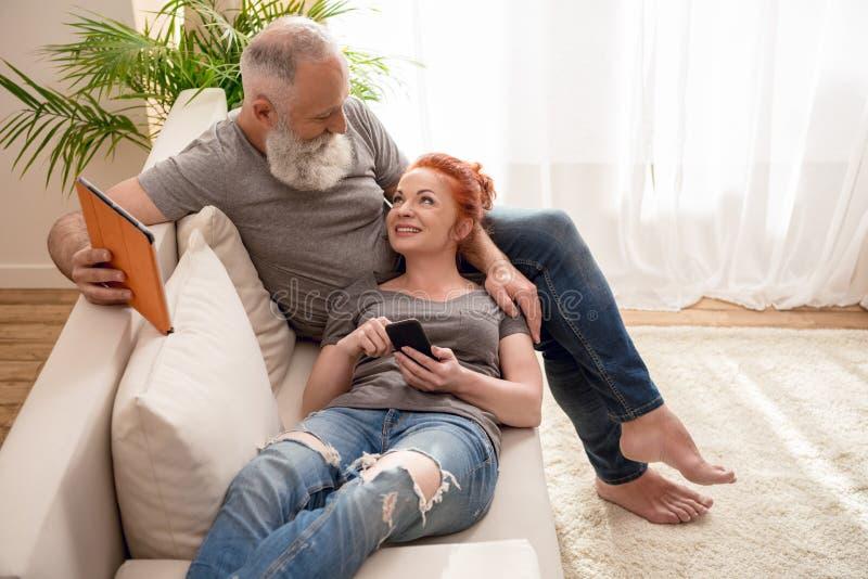在家微笑成熟的夫妇拿着数字式设备和 库存图片