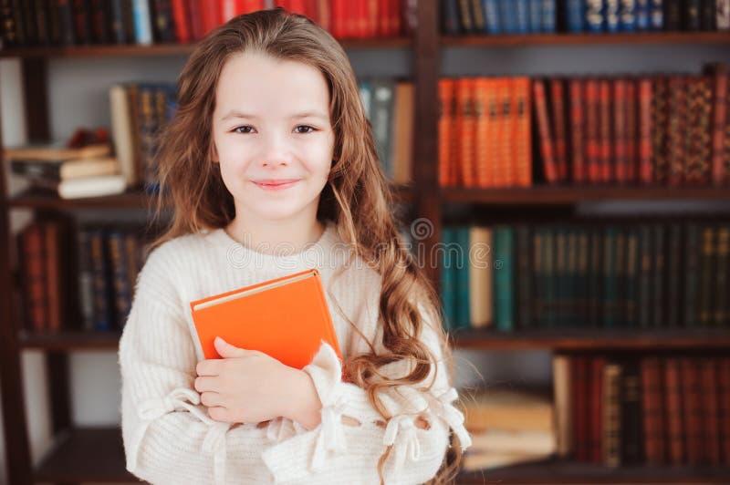 在家愉快的聪明的女小学生阅读书在图书馆或 免版税库存照片