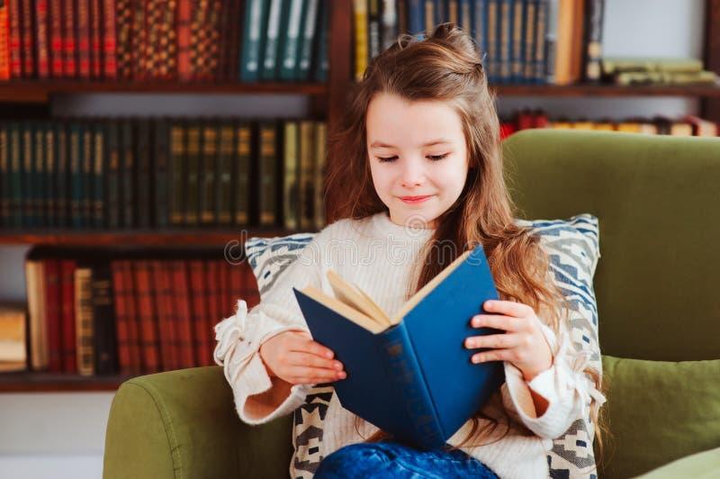 在家愉快的聪明的女小学生阅读书在图书馆或 免版税库存图片