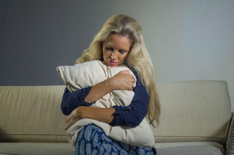 在家感觉被挫败的开会沙发长沙发哀伤的a的40s沮丧的和急切美丽的白肤金发的妇女遭受的消沉和痛苦 免版税库存图片