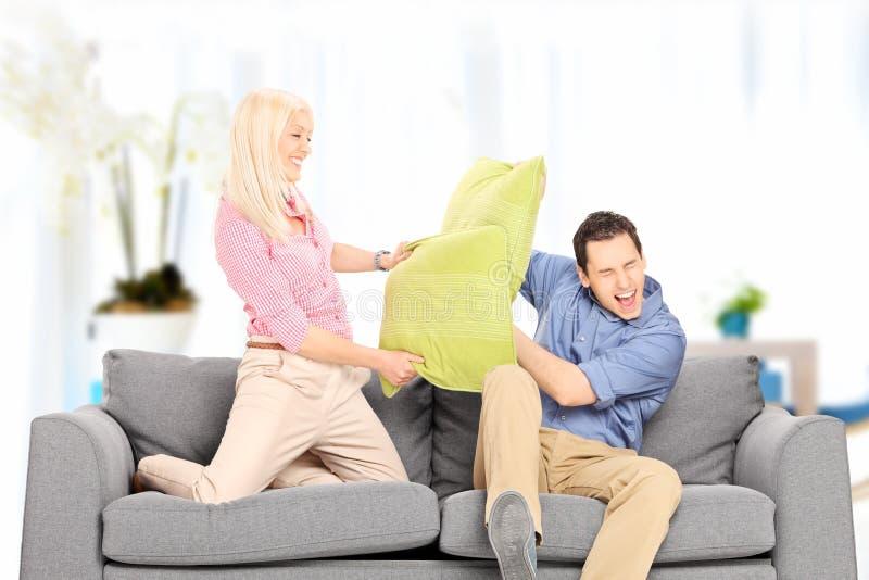在家战斗与枕头的年轻夫妇 库存照片