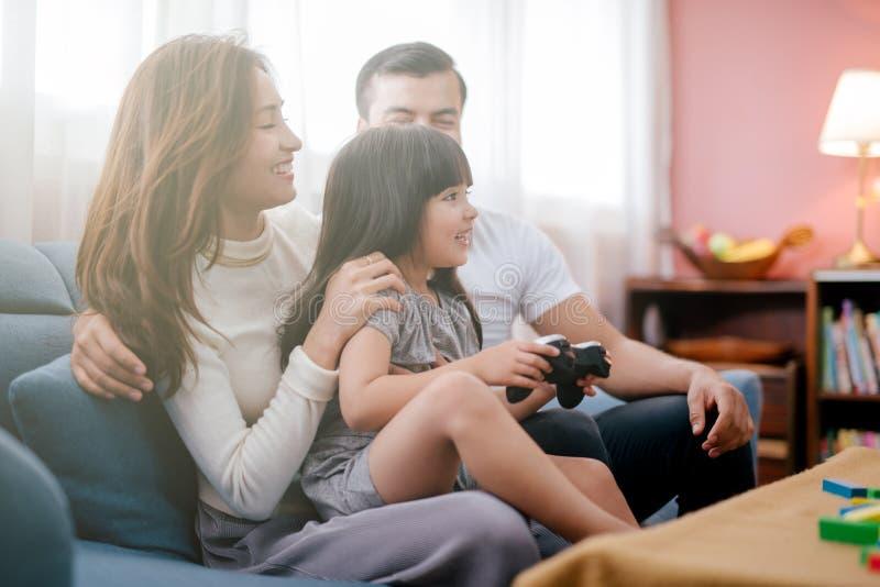 在家打电子游戏的女孩和父母家庭 免版税库存照片