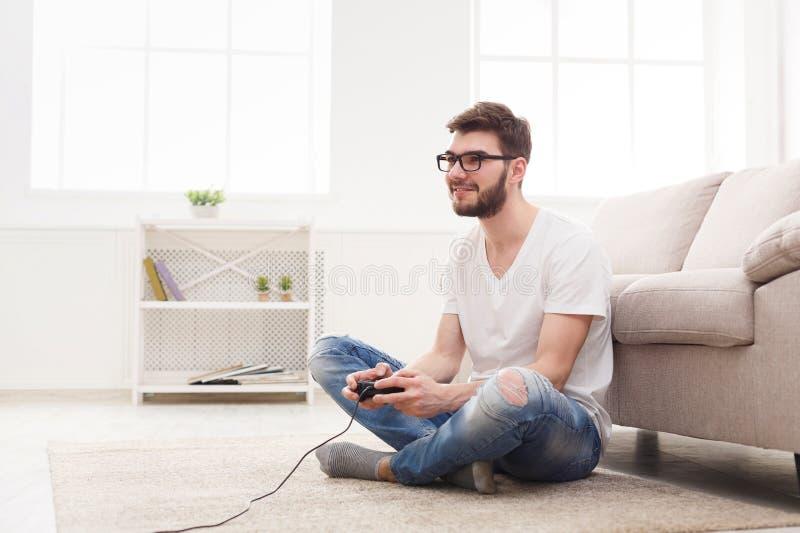 在家打电子游戏的愉快的年轻人 免版税库存图片