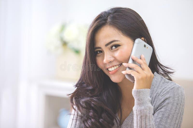 在家打电话的偶然亚裔妇女使用巧妙的电话 免版税图库摄影