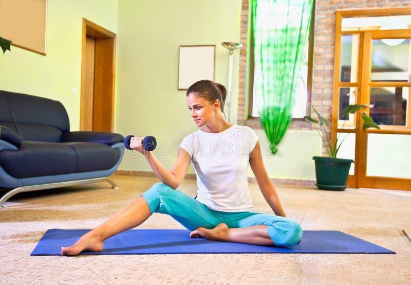 在家执行健身的愉快的少妇。 免版税库存图片