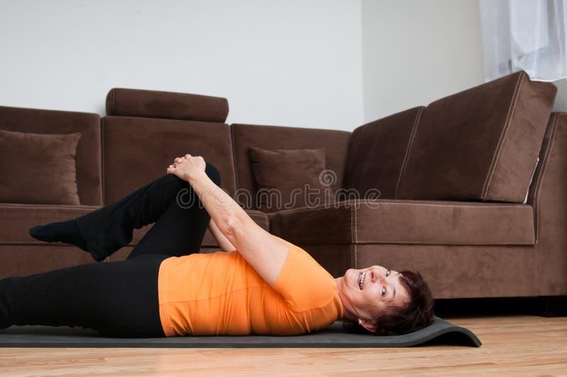 在家执行成熟健身的妇女 免版税库存照片