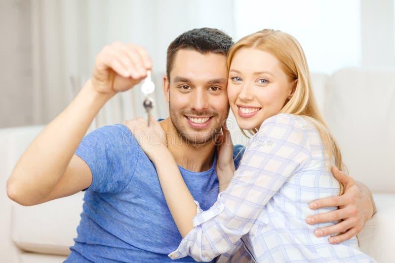 在家把握关键的微笑的夫妇 库存图片