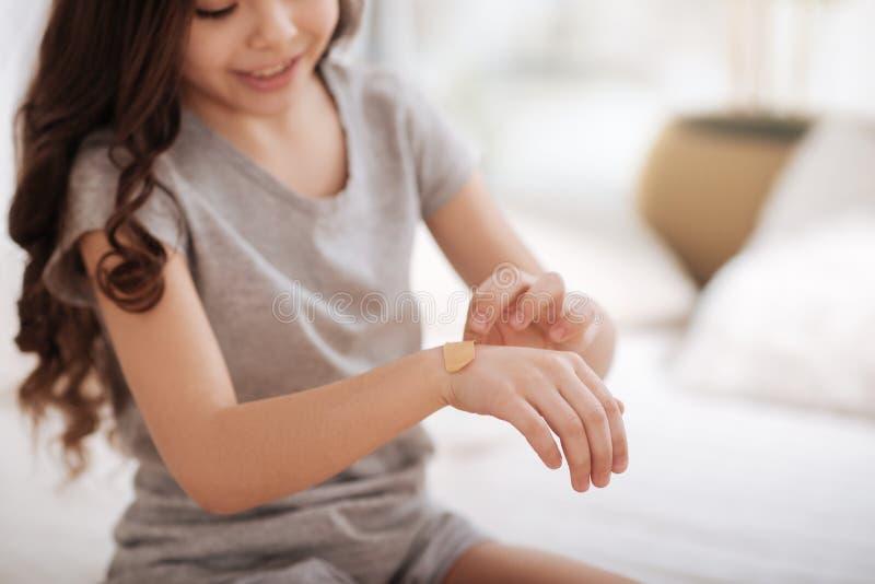 在家把援助膏药放的被集中的女孩在她的裁减上 免版税库存照片