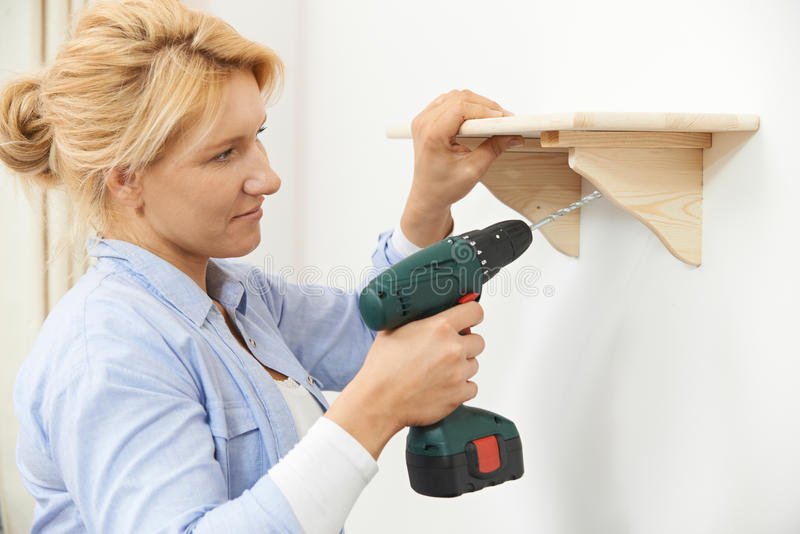 在家投入木架子的妇女使用无绳的钻子 库存照片