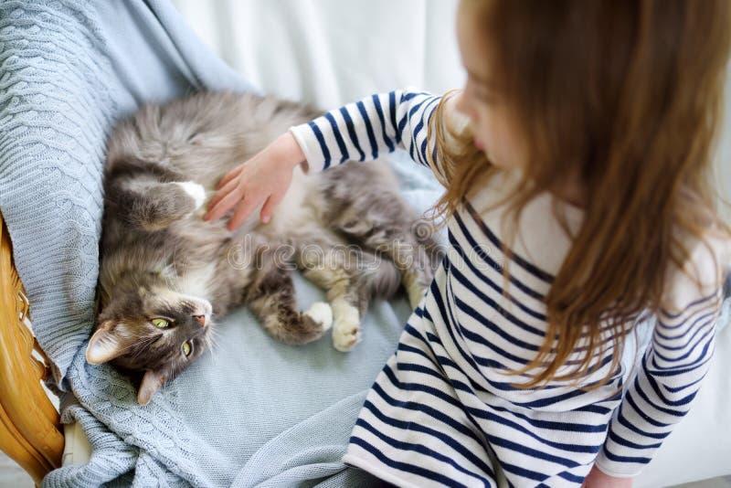在家抚摸她的宠物猫的小女孩 库存图片