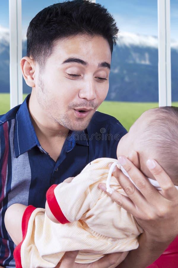 在家抱着婴孩的愉快的年轻父亲 库存图片