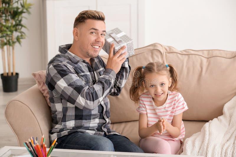 在家招呼逗人喜爱的女孩她的爸爸与父亲节 库存照片