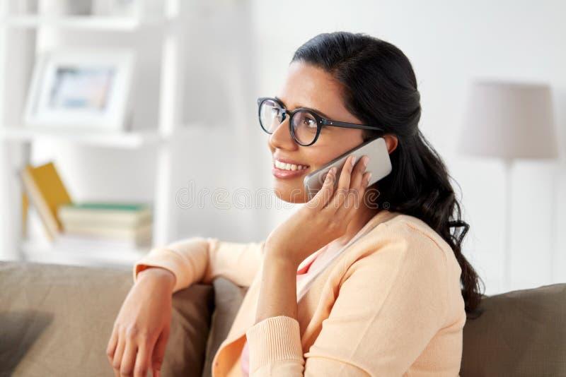 在家拜访智能手机的愉快的印地安妇女 免版税图库摄影