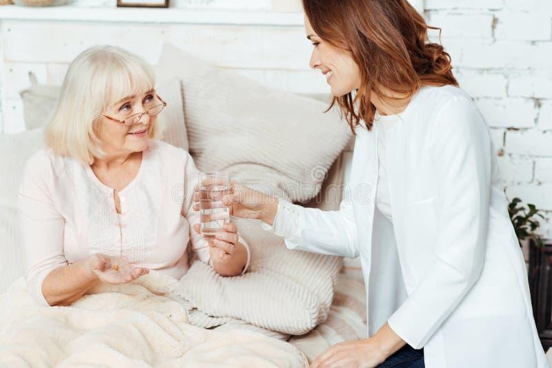 在家拜访病的妇女的正面护士 免版税库存图片