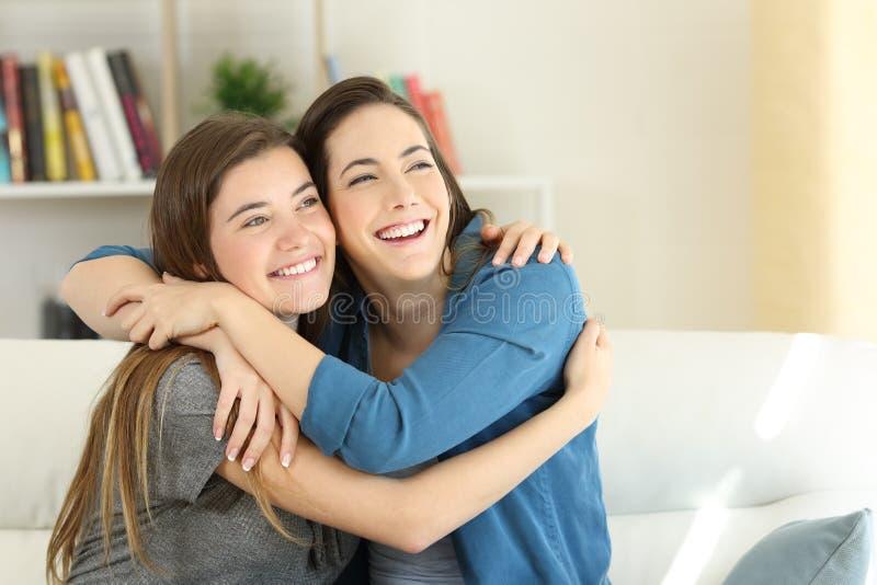 在家拥抱两个愉快的朋友或的姐妹 免版税图库摄影