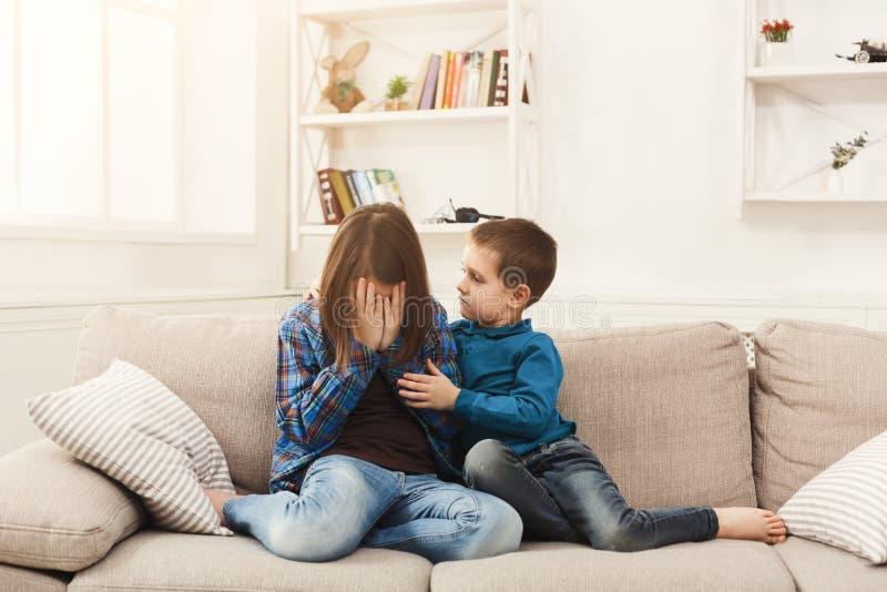 在家拥抱他哭泣的姐妹的男孩 免版税库存图片