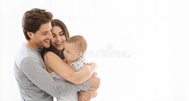 在家拥抱可爱的千福年的家庭,空的空间 库存图片