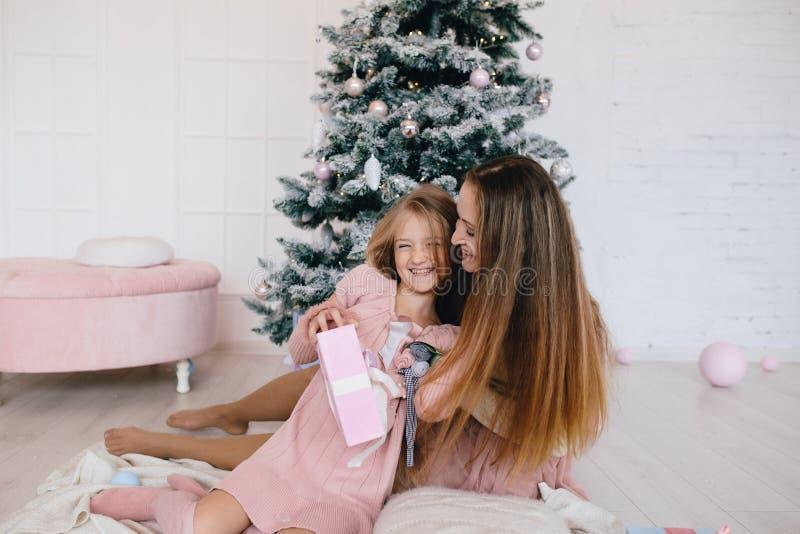 在家拥抱在圣诞树附近的母亲和女儿 妇女和女孩有圣诞节礼物的 库存照片