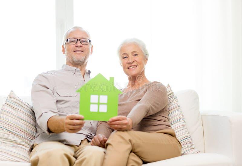 在家拥抱在沙发的愉快的资深夫妇 库存照片
